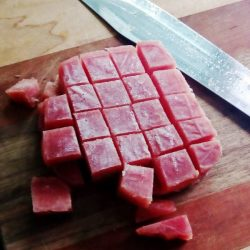Sashimi grade Ahi Tuna sliced in cubes for a Poke Bowl.