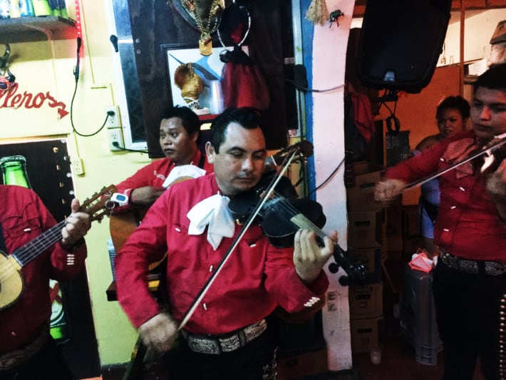 A mariachi band dressed in red button down shirts and black pants play string instruments at one of the best cantinas in Cozumel, La Revancha.