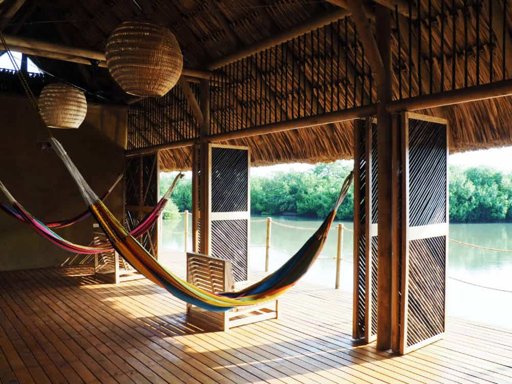 Hammocks hang under the palapa structure overlooking the mangrove lagoon.