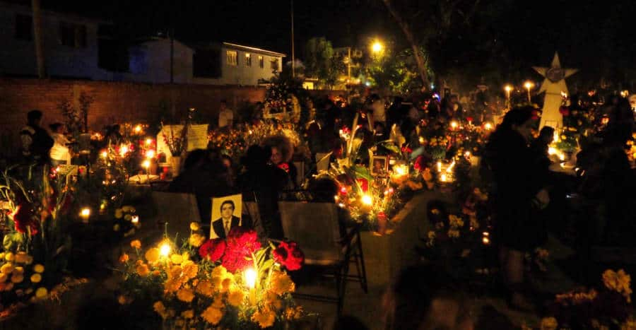 Day of the Dead celebration at the cemetery in Xoxo, Oaxaca. Graves are decorated and candles are lit.
