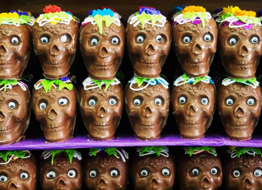 Chocolate Day of the Dead skulls line the shelf at a candy store.
