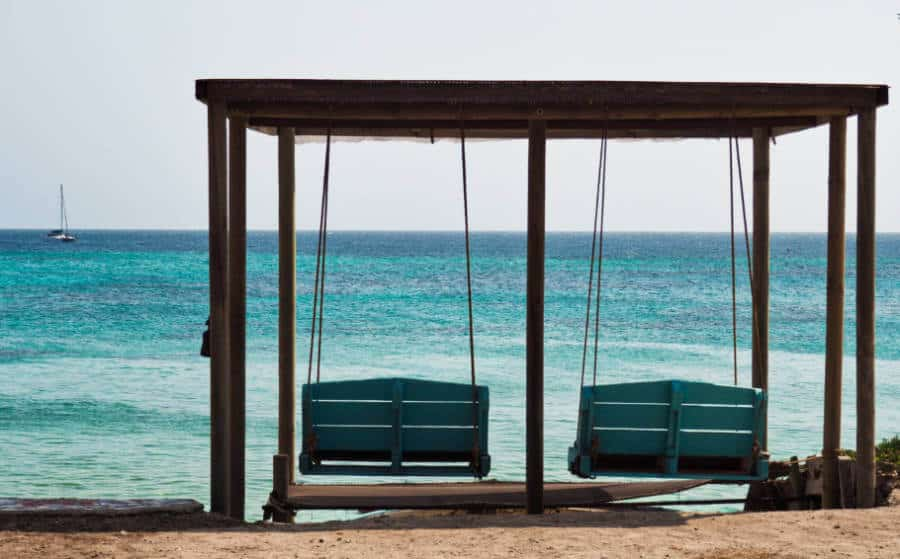 Wooden porch swings overlook the blue ocean at El Hamaquero as a sailboat passes by in the distance.