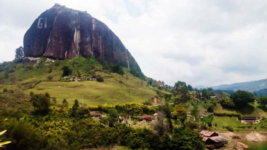 The Guatape rock juts out of the green hillside with a few cabins below.
