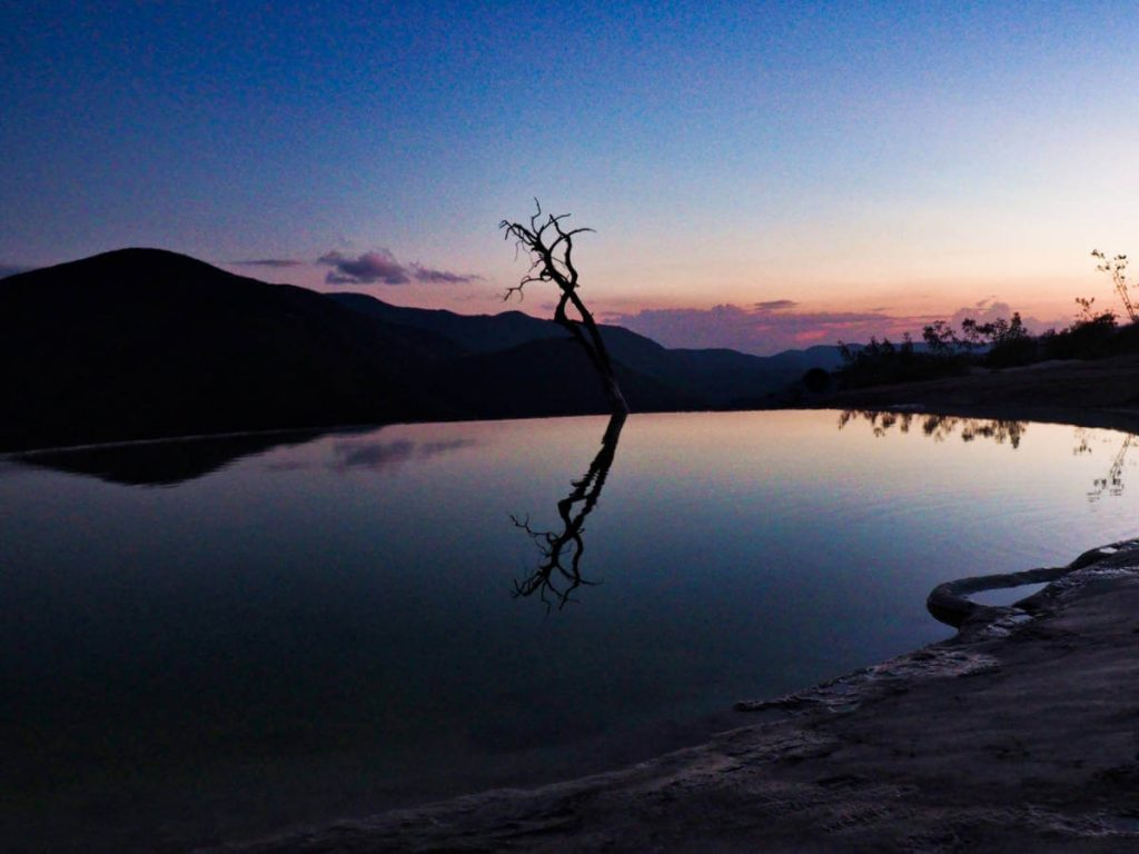 Silhouette of the infinity pool, tree, and surrounding mountains at sunset in Hierve el Agua, Oaxaca,