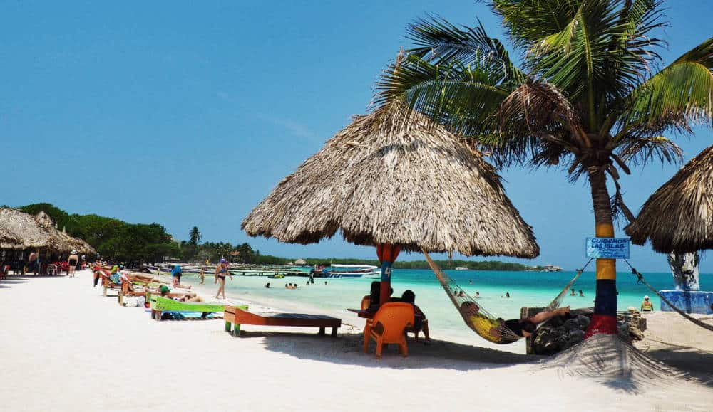 During a stop to Tintipan, a man enjoys a siesta in a shaded hammock hanging between a palapa and palm tree.