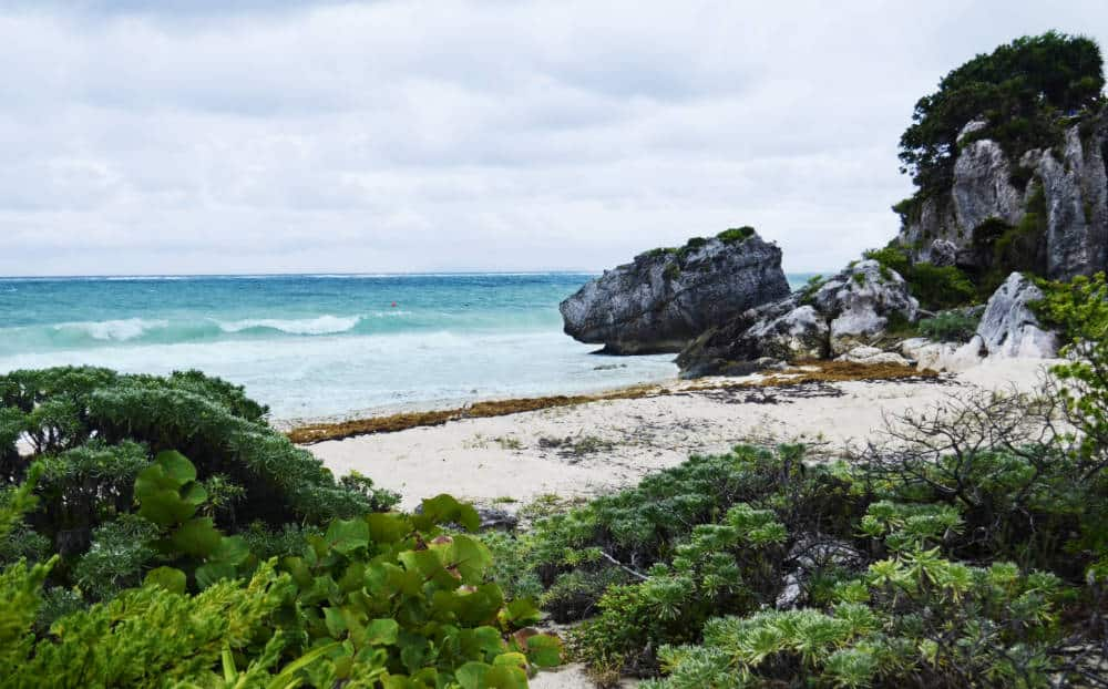 From the Tulum Mayan Ruins, a view of the cliff descending into the Caribbean Sea with sand in the foreground.