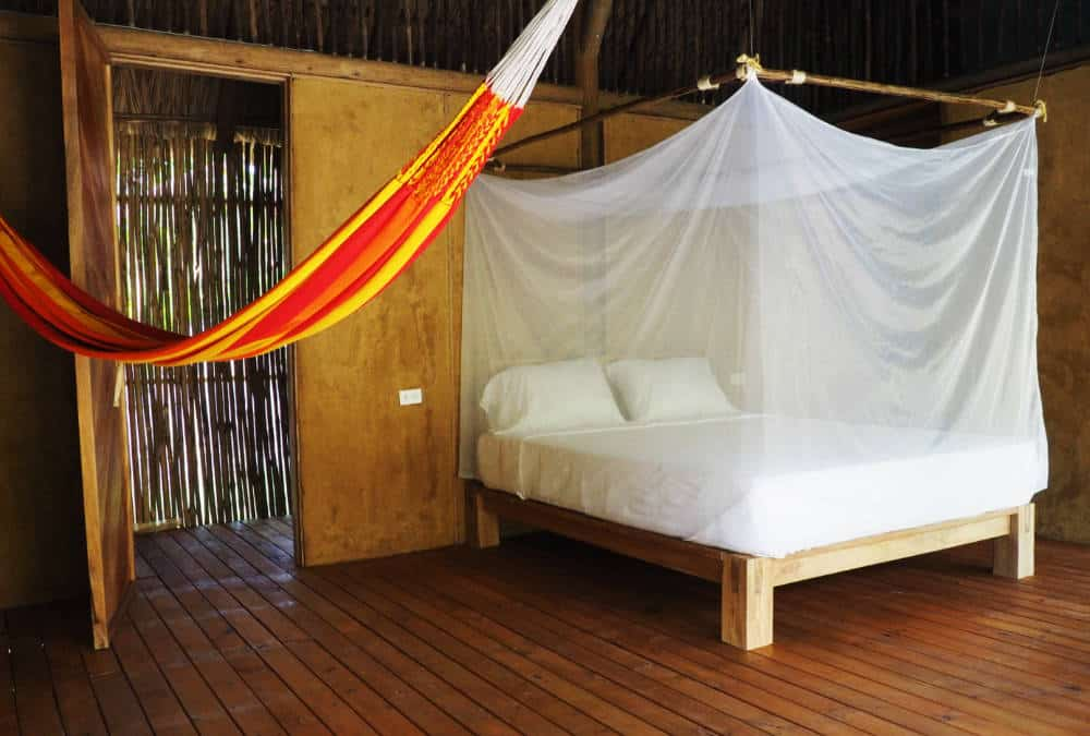 In Rincon del Mar, a hammock hangs next to the bed which is protected with a mosquito net.