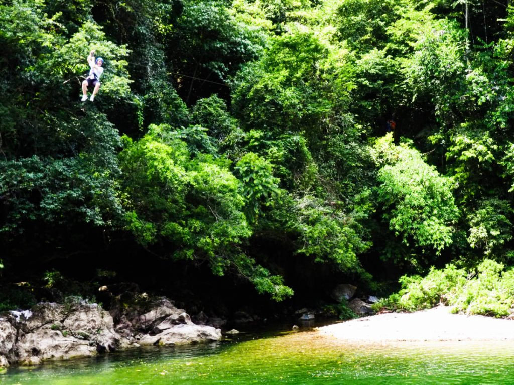 A young boy zip lines through the canopy and over the river at Playa Marmol.